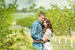 Os pares felizes novos atrativos em uma mola jardinam Foto de Stock
