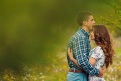 Os pares felizes novos atrativos em uma mola jardinam Fotos de Stock Royalty Free