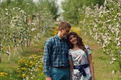 Os pares felizes novos atrativos em uma mola jardinam Fotografia de Stock