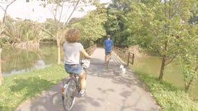Os pares felizes novos do moderno montam bicicletas retros no parque com o cão que corre próximo Ciclagem com animal de estimação filme