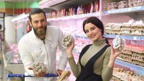 Os pares felizes novos escolhem ovos de codorniz no supermercado video estoque