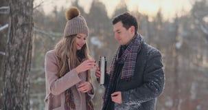 Os pares felizes que guardam copos de chá quentes sobre o inverno ajardinam Pares novos no amor em umas férias do inverno, estand filme