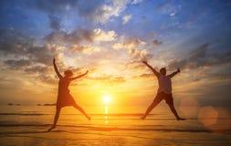 Os pares felizes que saltam no mar encalham durante um por do sol bonito Fotos de Stock