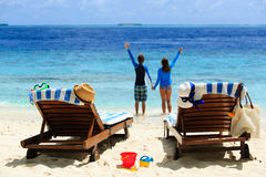 Os pares felizes relaxam em uma praia tropical Fotos de Stock Royalty Free
