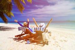 Os pares felizes relaxam em uma praia tropical Imagens de Stock