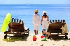 Os pares felizes relaxam em uma praia tropical da areia Imagens de Stock Royalty Free