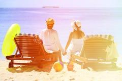 Os pares felizes relaxam em uma praia tropical da areia Fotos de Stock