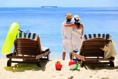 Os pares felizes relaxam em uma praia tropical da areia Fotografia de Stock Royalty Free