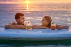 Os pares felizes relaxam na placa de pá no por do sol Imagem de Stock