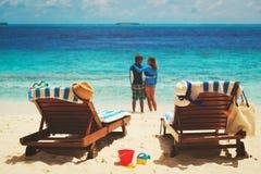 Os pares felizes relaxam na praia tropical Fotografia de Stock