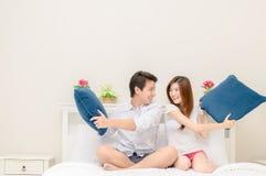 Os pares felizes sorriem e jogando na cama em casa fotografia de stock royalty free