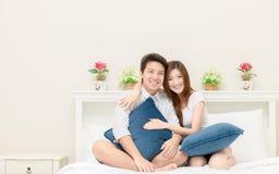 Os pares felizes sorriem e jogando na cama em casa, no amor e no romanti fotos de stock royalty free