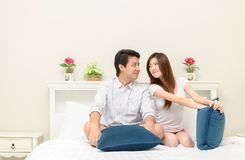 Os pares felizes sorriem e jogando na cama em casa, no amor e no romanti imagens de stock royalty free