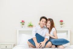 Os pares felizes sorriem e jogando na cama em casa, no amor e no romanti fotos de stock