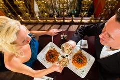 Os pares felizes têm uma data romântica no restaurante foto de stock