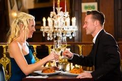 Os pares felizes têm uma data romântica no restaurante fotos de stock