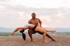 Os pares ginásticos da raça misturada com corpos perfeitos na dança do sportswear em montanhas ajardinam o fundo Céu cor-de-rosa  fotos de stock royalty free