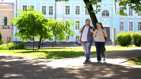 Os pares gordos do estudante que andam na cidade estacionam, data urbana, tempo de lazer, amizade imagem de stock