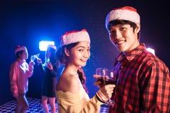Os pares, os homens e as mulheres asiáticos comemoram a estação da festa de Natal imagens de stock