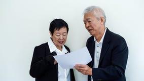 Os pares idosos asiáticos do sorriso feliz no negócio attire, proprietário do SME imagens de stock