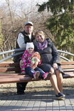 Os pares idosos felizes com a neta sentam-se em um banco no th Imagem de Stock