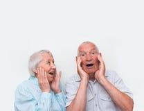 Os pares idosos surpreendidos levantando ambas as mãos Fotos de Stock