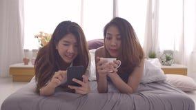 Os pares lésbicas asiáticos felizes bonitos são pijamas do desgaste usando o smartphone para verificar a notícia e conversar e o  filme