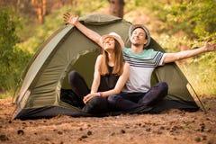 Os pares levantaram suas mãos até a luz solar na floresta verde perto da barraca Conceito de f?rias ativas foto de stock