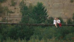 Os pares loving de turistas são de beijo e de fala ao sentar-se na ponte de madeira de suspensão nas montanhas zangão video estoque