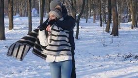 Os pares loving em um parque nevado, homem novo de inquietação cobriram sua amiga com uma cobertura filme