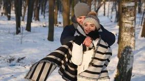 Os pares loving em um parque nevado, homem novo de inquietação cobriram sua amiga com uma cobertura video estoque
