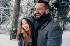 Os pares loving felizes que andam na floresta nevado do inverno, gastando o Natal vacation junto Atividades sazonais exteriores fotografia de stock