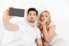 Os pares loving novos alegres fazem o selfie perto pelo telefone fotografia de stock royalty free