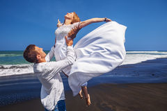 Os pares loving novos têm um divertimento na praia da areia do preto do mar Fotografia de Stock