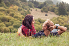 Os pares loving oferecem a conversação no prado verde no país imagem de stock royalty free