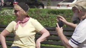 Os pares maduros à moda olham as fotos na câmera que senta-se no banco no parque vídeos de arquivo