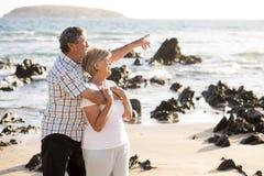 Os pares maduros superiores bonitos em seu 60s ou 70s aposentaram-se o passeio feliz e relaxado na costa de mar da praia no envel Foto de Stock Royalty Free