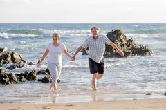 Os pares maduros superiores bonitos em seu 60s ou 70s aposentaram-se o passeio feliz e relaxado na costa de mar da praia no envel Fotos de Stock Royalty Free