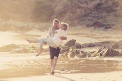 Os pares maduros superiores bonitos em seu 60s ou 70s aposentaram-se o passeio feliz e relaxado na costa de mar da praia no envel Fotos de Stock