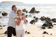 Os pares maduros superiores bonitos em seu 60s ou 70s aposentaram-se o passeio feliz e relaxado na costa de mar da praia no envel Fotografia de Stock Royalty Free