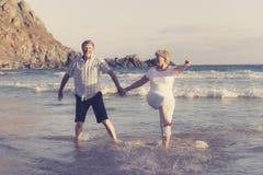 Os pares maduros superiores bonitos em seu 60s ou 70s aposentaram-se o passeio feliz e relaxado na costa de mar da praia no envel Foto de Stock