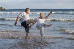 Os pares maduros superiores bonitos em seu 60s ou 70s aposentaram-se o passeio feliz e relaxado na costa de mar da praia no envel Imagem de Stock