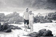 Os pares maduros superiores bonitos em seu 60s ou 70s aposentaram-se o passeio feliz e relaxado na costa de mar da praia no envel Fotografia de Stock