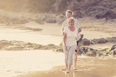 Os pares maduros superiores bonitos em seu 60s ou 70s aposentaram-se o passeio feliz e relaxado na costa de mar da praia no envel Imagens de Stock