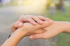 Os pares mantêm as mãos unidas no jardim do amor imagens de stock