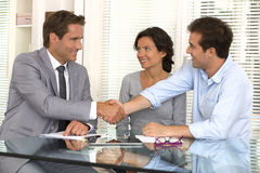 Os pares modernos felizes selam um negócio com seu anúncio financeiro pessoal Imagem de Stock Royalty Free
