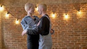 Os pares modernos novos de modernos são dançar, abraçando, conceito do amor, fundo do tijolo video estoque
