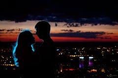 Os pares mostram em silhueta na cidade da noite fotos de stock royalty free