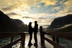 Os pares mostram em silhueta no lago da montanha Fotos de Stock