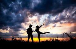 Os pares mostram em silhueta no por do sol Fotografia de Stock